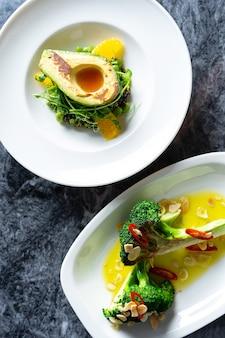 Draufsicht auf leckeres und luxuriöses essen mit restaurant-food-stil auf marmortisch. frische und gegrillte gemüsesalate mit avocado, brokkoli in weißem teller.