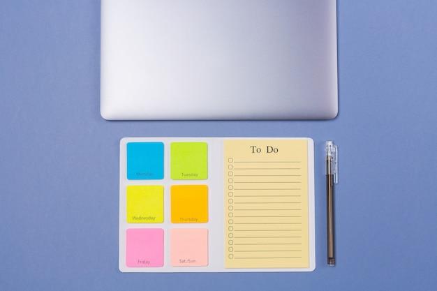 Draufsicht auf leere aufgabenliste für die woche, stift und laptop auf hellviolettem hintergrund, flache lage. speicherplatz kopieren. freiraum. zeitplan. zeitplan.