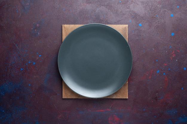 Draufsicht auf leere dunkle platte rund auf der dunklen oberfläche gebildet