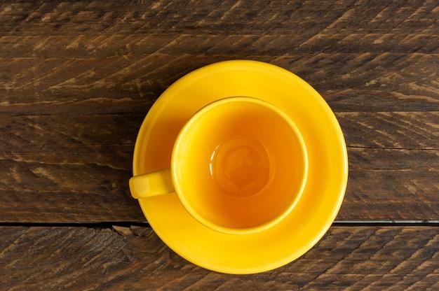 Draufsicht auf leere gelbe tasse und untertasse auf rustikalem holzboden. küchengeschirr.