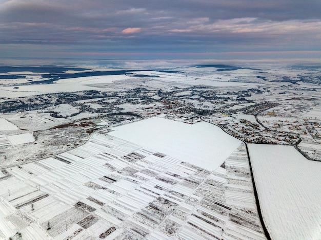 Draufsicht auf leere schneebedeckte felder am wintermorgen auf dramatischem bewölktem himmelhintergrund. konzept der luftdrohnenfotografie.