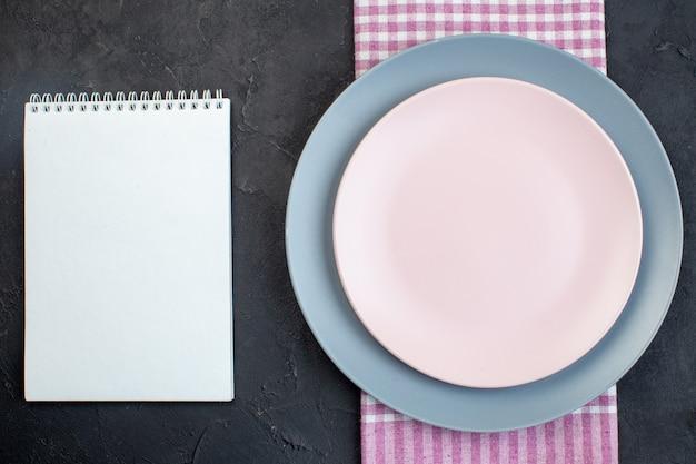Draufsicht auf leere weiße und blaue keramikplatten auf gefaltetem rosafarbenem handtuch und notizbuch auf schwarzem hintergrund mit freiem platz