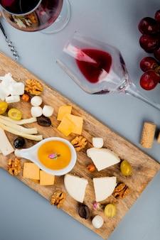 Draufsicht auf liegendes glas rotwein mit verschiedenen arten von käsetrauben-oliven-nussbutter auf schneidebrett und kork auf weiß