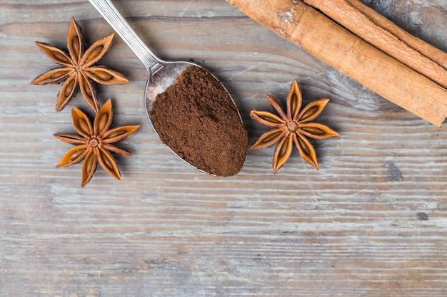 Draufsicht auf löffel mit gemahlenem kaffee und aromatischen gewürzen