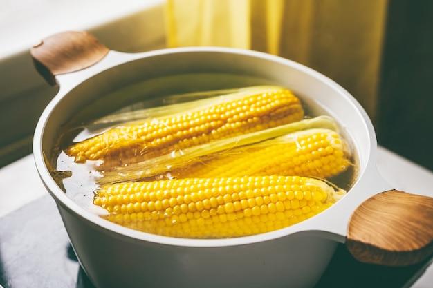 Draufsicht auf maiskolben, die in einem topf kochen. gesundes vegetarisches ernährungskonzept