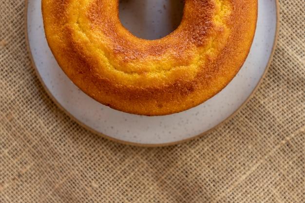 Draufsicht auf maiskuchen mit orange auf weißem teller und jutetischdecke.