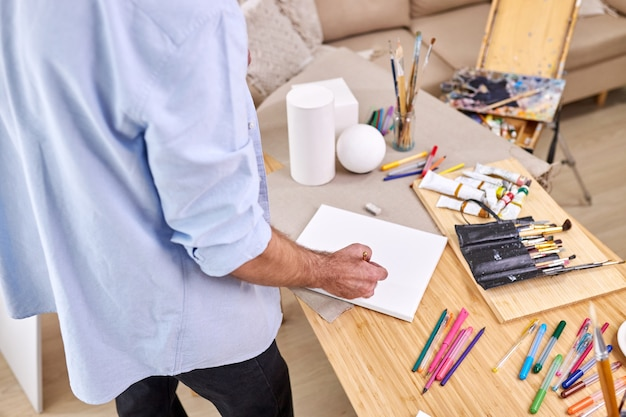 Draufsicht auf malermann, der blätter, bleistifte und andere werkzeuge zum malen am tisch verwendet