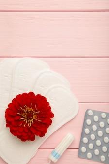Draufsicht auf menstruationspads, tampons und pillen für periodenschmerzen mit roter blume auf rosafarbenem holzhintergrund. vertikales foto.