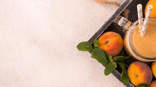 Draufsicht auf milchshake mit pfirsichen und strohhalmen