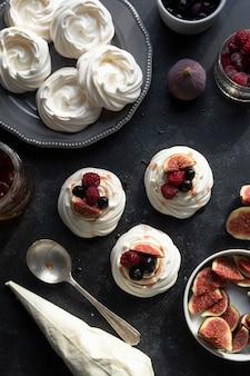 Draufsicht auf mini-pavlova-baiser-kuchen, verziert mit beeren und feigen