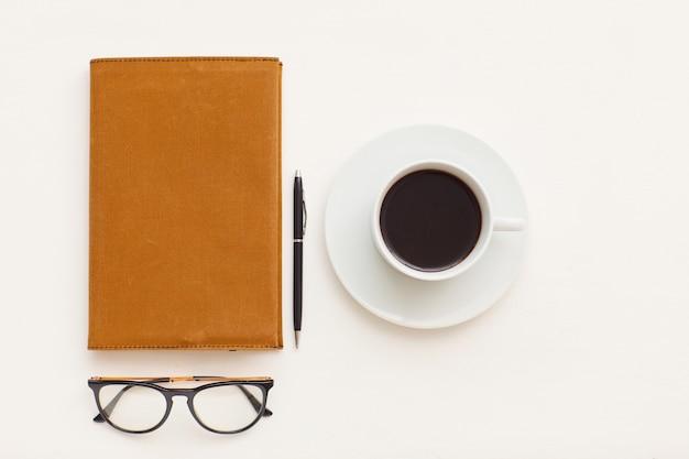 Draufsicht auf minimale zusammensetzung einer einzelnen kaffeetasse neben geschäftsplaner und gläsern mit schwarzem rand