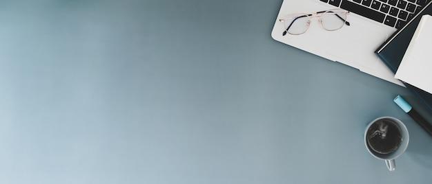 Draufsicht auf minimalen arbeitsplatz mit laptop, brille, kaffeetasse und notebook auf grauem tisch. kopieren sie platz für werbetext.