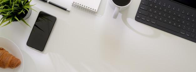 Draufsicht auf minimalen arbeitstisch mit smartphone, tablet, zubehör, frühstücksmahlzeit und kopierraum