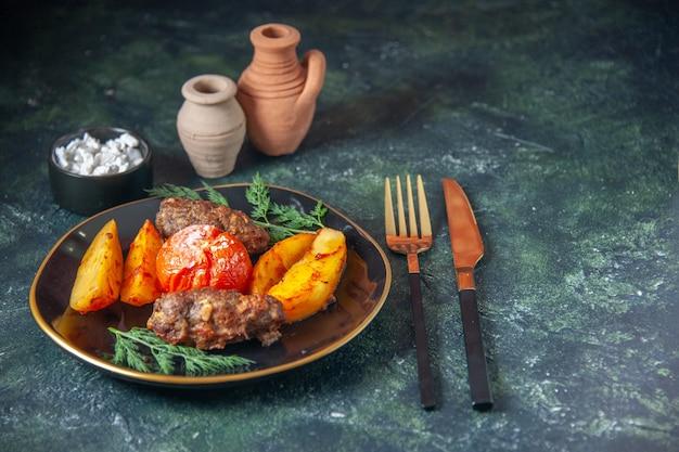 Draufsicht auf mit kartoffeln und tomaten gebackene fleischkoteletts, serviert mit grünem besteck, salz auf dunklem hintergrund