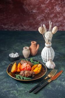 Draufsicht auf mit kartoffeln und tomaten gebackene fleischkoteletts, serviert mit grünem besteck, salzknoblauch auf mischfarbenhintergrund