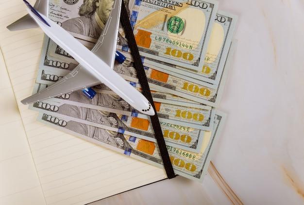 Draufsicht auf modellflugzeug, notizbuch und us-dollar-scheine