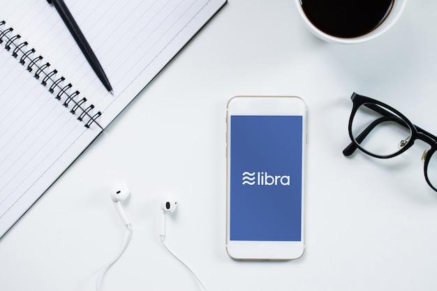 Draufsicht auf moderne technologie, die auf einem smartphone mit weißem bildschirm und dem facebook-kryptowährungssymbol libra funktioniert.