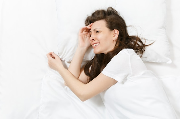 Draufsicht auf müde gestresste weinende junge brünette frau, die mit weißem laken, kissen, decke im bett liegt. geschockte frustrierte traurige verärgerte frau liegt auf ihrer seite