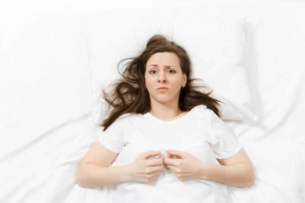Draufsicht auf müde gestresste weinende junge frau, die mit weißem laken, kissen, decke im bett liegt. nachdenkliche frustrierte traurige verärgerte frau, die zeit im zimmer verbringt