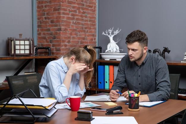 Draufsicht auf müde junge arbeiterin und ihren männlichen kollegen, die in büroumgebung am tisch sitzen