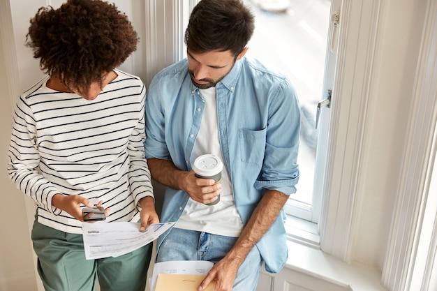 Draufsicht auf multiethnische manager diskutieren marketingbericht, arbeiten zusammen, überprüfen informationen auf handy getränk zum mitnehmen kaffeeständer gegen fensterwand. unrasierter mann und sein assistent
