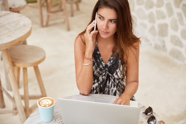 Draufsicht auf nachdenkliche attraktive frau hat nachdenklichen ausdruck, während gespräche über smartphone mit geschäftspartner, fernarbeit auf laptop-computer, genießt aromatischen cappuccino im café