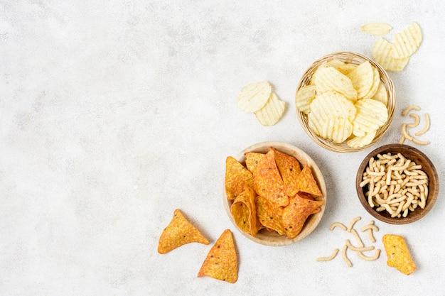 Draufsicht auf nacho-chips und kartoffelchips mit kopierraum