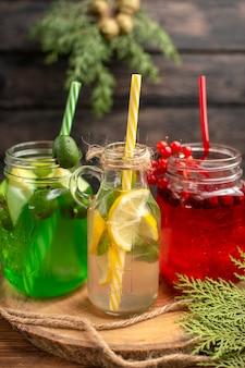 Draufsicht auf natürliche bio-früchtesäfte in flaschen, die mit röhren auf einem holzbrett serviert werden