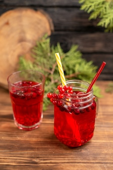 Draufsicht auf natürlichen organischen frischen johannisbeersaft in einer flasche mit tuben und in einem glas auf einem holztisch a
