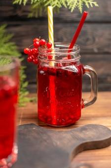 Draufsicht auf natürlichen organischen frischen johannisbeersaft in einer glasflasche, die mit röhren auf einem holzschneidebrett serviert wird