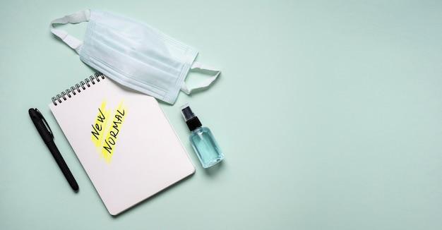Draufsicht auf notizbuch mit neuer normaler und medizinischer maske