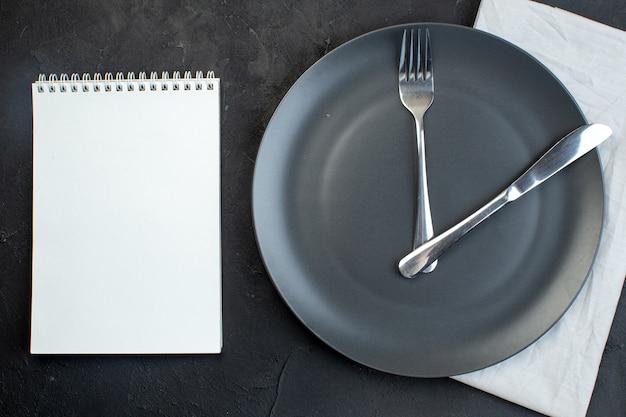 Draufsicht auf notizbuch und besteck auf einer schwarzen platte auf weißem handtuch auf dunklem hintergrund mit freiem platz