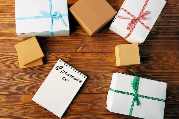 Draufsicht auf notizbuch und geschenkboxen mit bändern auf holztischpapier mit aufschrift...