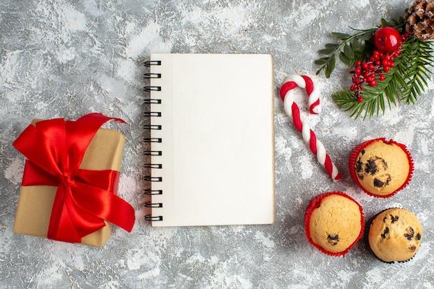 Draufsicht auf notizbuch und kleine cupcakes süßigkeiten und tannenzweige dekorationszubehör und geschenk mit rotem band auf eisoberfläche