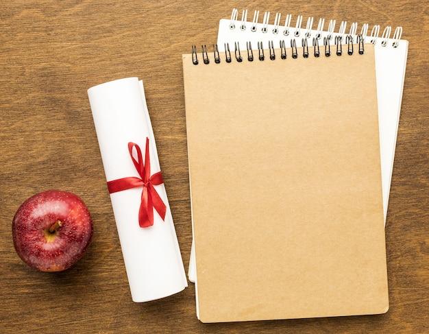 Draufsicht auf notizbücher mit diplom und apfel
