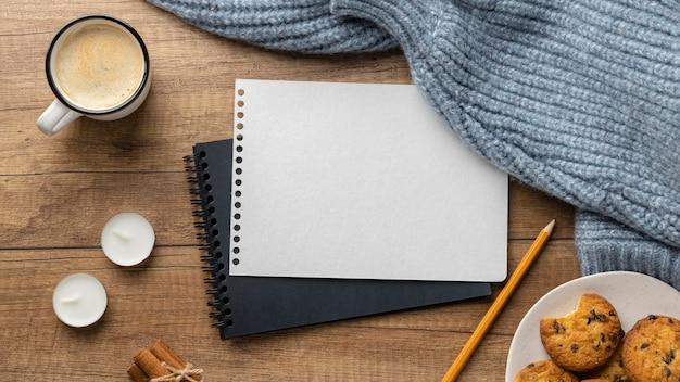 Draufsicht auf notizbücher mit tasse kaffee und pullovern