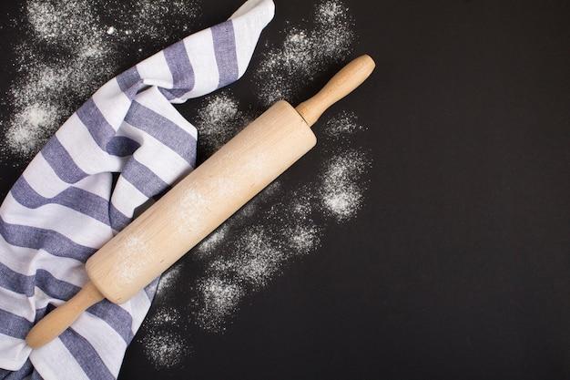 Draufsicht auf nudelholz und weißmehl auf dunkler oberfläche. küchenhintergrund.
