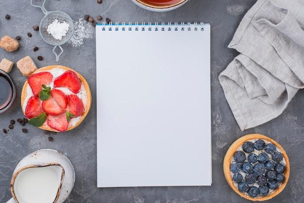 Draufsicht auf obstkuchen mit notizbuch
