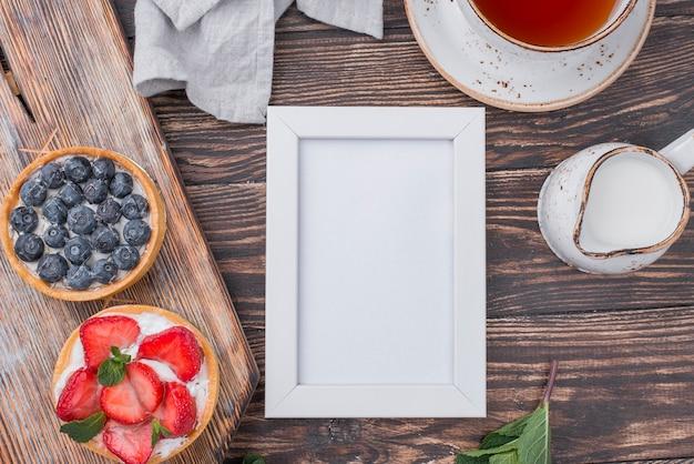 Draufsicht auf obstkuchen mit tee und rahmen