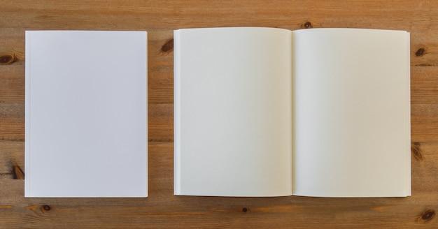 Draufsicht auf offene leeres buch neben einem stück papier