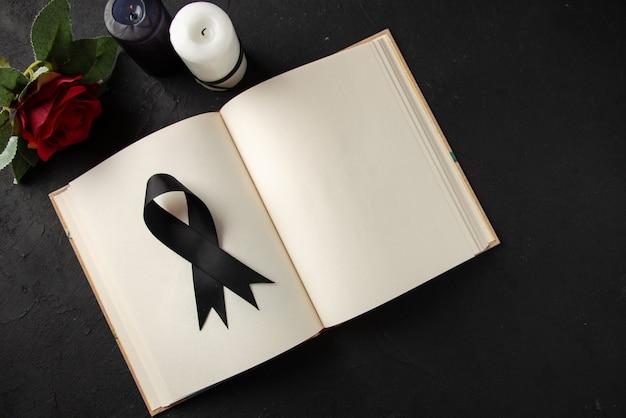 Draufsicht auf offenes buch mit schwarzer trauerschleife an dunkler wand