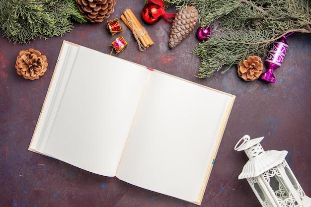 Draufsicht auf offenes heft mit weihnachtsbaum und zapfen auf schwarz