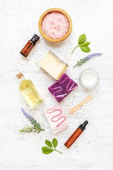 Draufsicht auf organische seifen und kosmetika, angeordnet mit lavendel, kräutern, chiasamen und ätherischen ölen.