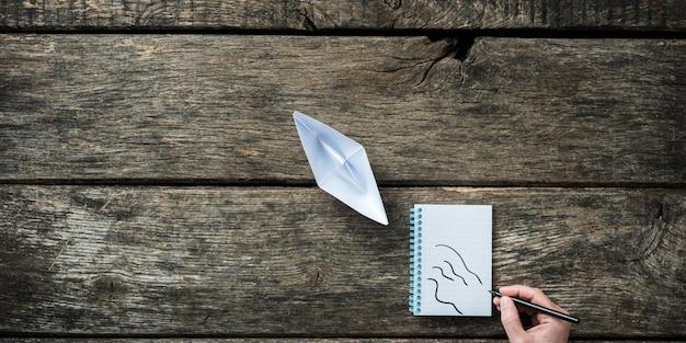 Draufsicht auf papier gemachtes origami-boot mit männlicher hand, die wasserwellen im notizblock dahinter zeichnet.