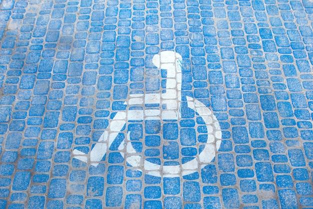 Draufsicht auf parkschild für behinderte. behindertenparkplatz und rollstuhlsymbole auf dem bürgersteig
