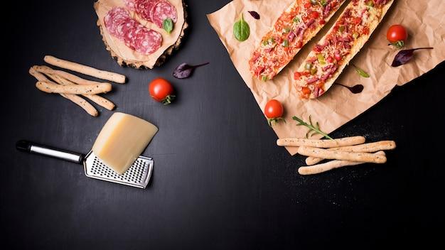 Draufsicht auf peperoni-scheiben; brotstöcke; käse; tomaten- und baguettepizza auf braunem papier über schwarzer arbeitsplatte