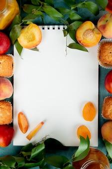 Draufsicht auf pfirsiche cupcakes pfirsichmarmelade mit notizblock in der mitte auf blau verziert mit blättern mit kopierraum