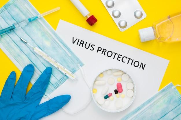 Draufsicht auf pillen in der schale zum virenschutz mit medizinischen masken und thermometer
