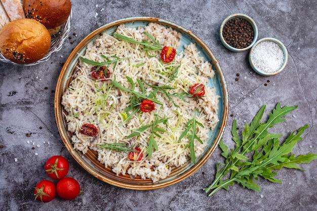 Draufsicht auf pilzrisotto, garniert mit geriebenem käse, getrockneten tomaten und blättern