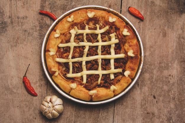 Draufsicht auf pizza mit rindfleisch und frischkäse, umgeben von chilis und knoblauch, serviert auf holztisch